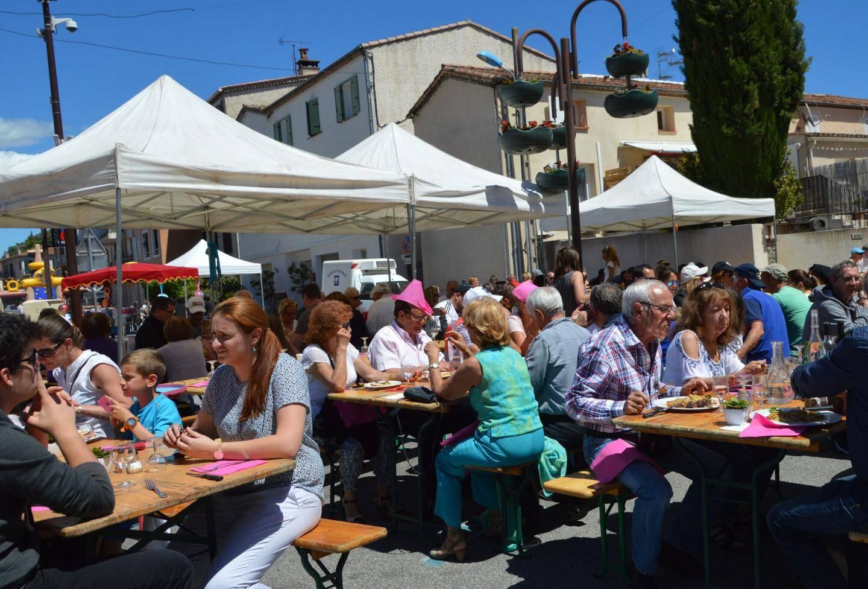 Beaucoup de monde aux terrasses installées dans la rue par deux restaurants.
