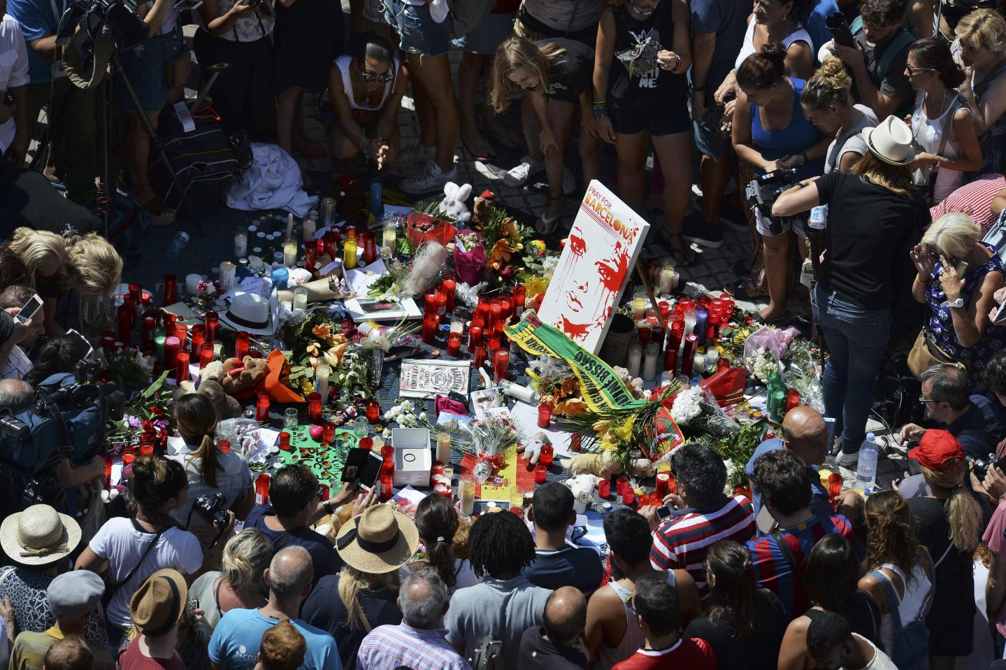 People gather to leave candles, flowers, messages, stuffed toys and many differents objects for the victims on August 18, 2017 at the spot where yesterday a van ploughed into the crowd, killing 14 persons and injuring over 100 on the Rambla boulevard in Barcelona.Drivers have ploughed on August 17, 2017 into pedestrians in two quick-succession, separate attacks in Barcelona and another popular Spanish seaside city, leaving 14 people dead and injuring more than 100 others. In the first incident, which was claimed by the Islamic State group, a white van sped into a street packed full of tourists in central Barcelona on Thursday afternoon, knocking people out of the way and killing 13 in a scene of chaos and horror. Some eight hours later in Cambrils, a city 120 kilometres south of Barcelona, an Audi A3 car rammed into pedestrians, injuring six civilians -- one of them critical -- and a police officer, authorities said. / AFP PHOTO / Josep LAGO SPAIN-ATTACK-BARCELONA