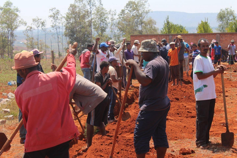 A Madagascar, les parents n'hésitent pas à prendre la pioche pour creuser les premières fondations de l'école.