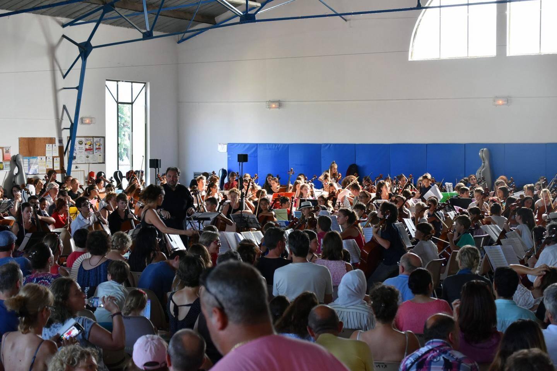 Frédéric Audibert entouré des 220 jeunes violoncellistes dans la salle des sports de Callian.