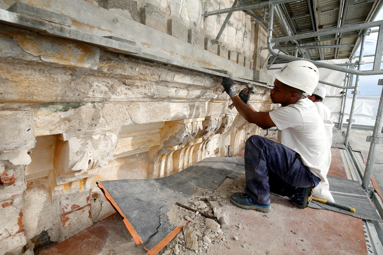 Les ouvriers spécialisés purgent les enduits des façades de la basilique pour parvenir à la couche initiale.