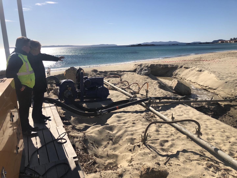 Gil Bernardi et Yves Brunetto devant l'ouvrage de rabattement de nappe et ses aiguilles plantées dans le sable.