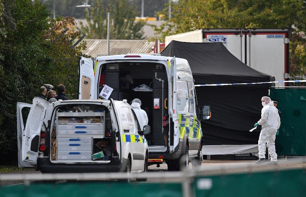 Des policiers britanniques en combinaisons près du camion frigorifique dans lequel 39 morts ont été découverts à Grays, à l'est de Londres, le 23 octobre 2019
