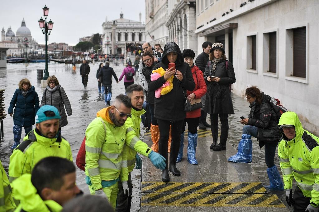 Des bénévoles érigent une passerelle pour les piétons à Venise le 13 novembre 2019 après une acqua alta d'une ampleur exceptionnelle