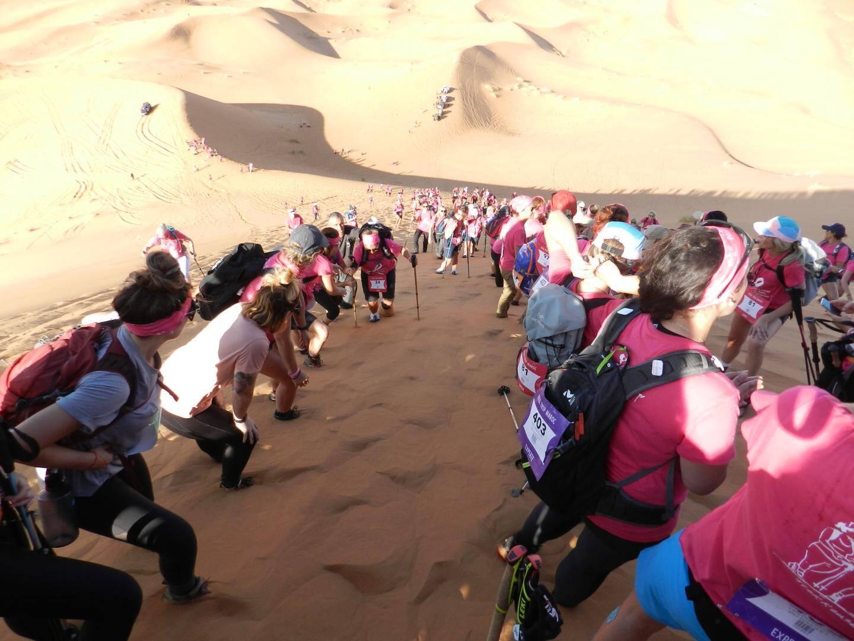 Le dernier jour les participantes s'entraident pour atteindre le sommet de la plus haute dune de Merzouga.