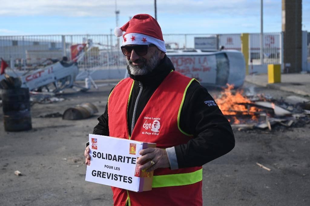 Un militant CGT porte une cagnotte pour les grévistes, lors d'un repas de noël organisé le 24 décembre 2019 au port de Marseille