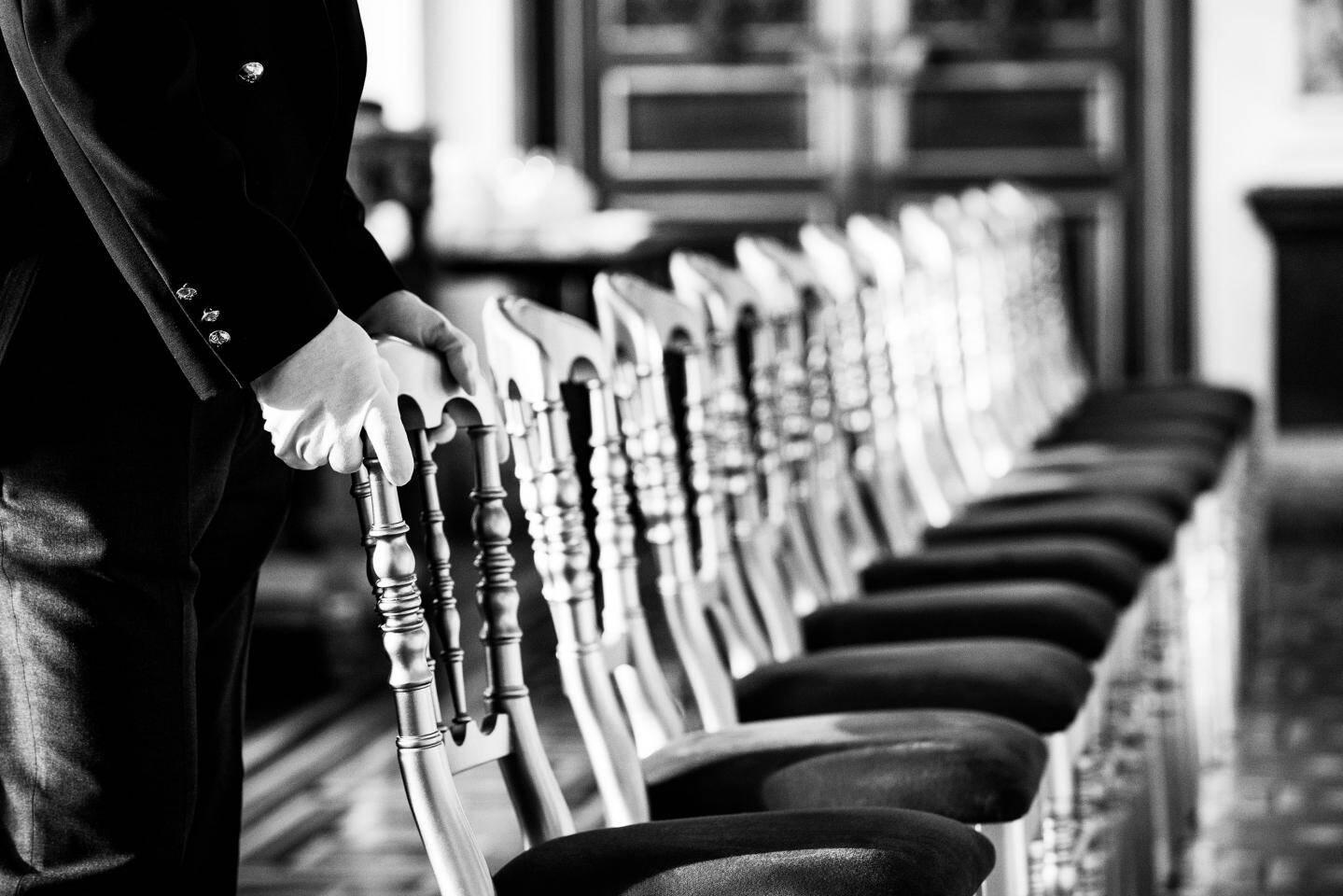 Des gants blancs en quête perpétuelle de la perfection, comme ici lors de la mise en place d'une réception par les valets.