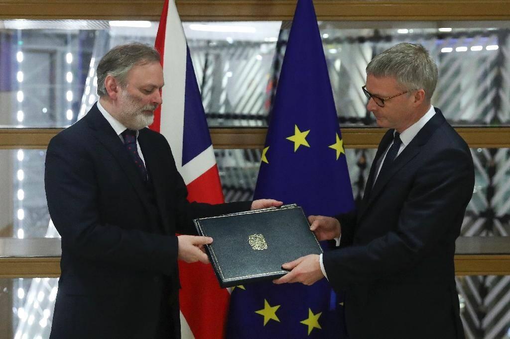 Le représentant du Royaume-Uni auprès de l'UE Tim Barrow remet le document officiel montrant que Londres a rempli ses obligations légales pour sortir de l'UE au Secrétaire général du Conseil européen Jeppe Tranholm-Mikkelsen le 29 janvier 2020 à Bruxelles
