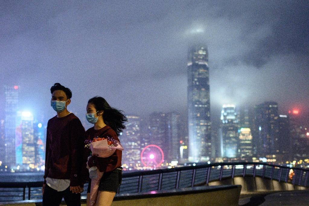 Un couple portant des masques de protection contre le nouveau coronavirus à Tsim Sha Tsui, à Hong Kong, le 14 février 2020