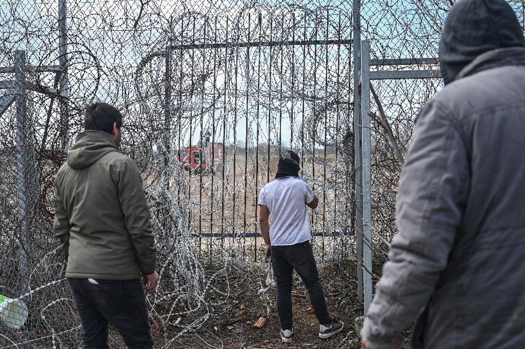 Des mirants se tiennent près des grilles au point de passage de Pazarkule à la frontière gréco-turque le 7 mars 2020
