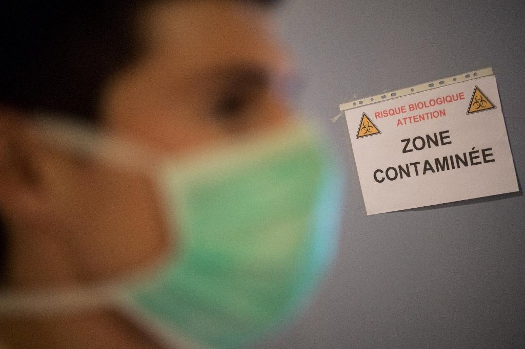 Un soignant passe devant une affiche de mise en garde à l'entrée d'un gymnase utilisé comme centre décontamination pour les personnels médicaux, le 6 avril 2020 à Trignac, en Loire-Atlantique