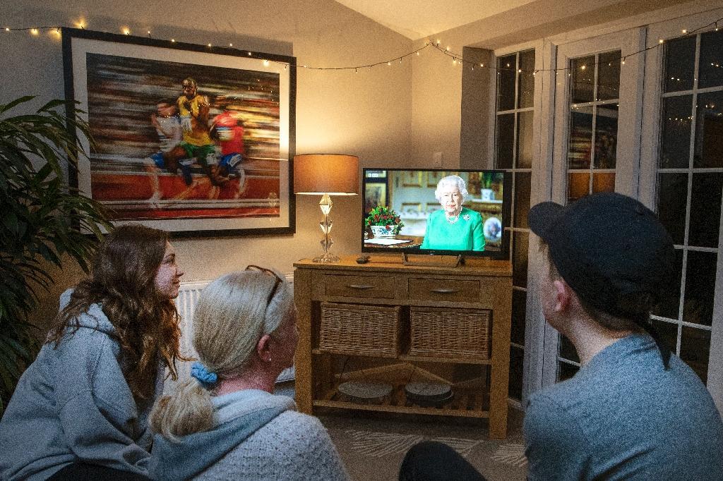 Une famille du village de Hartley Wintney (ouest de Londres) suit une rare allocution télévisée de la reine Elizabeth II   sur la pandémie de nouveau coronavirus, le 5 avril 2020