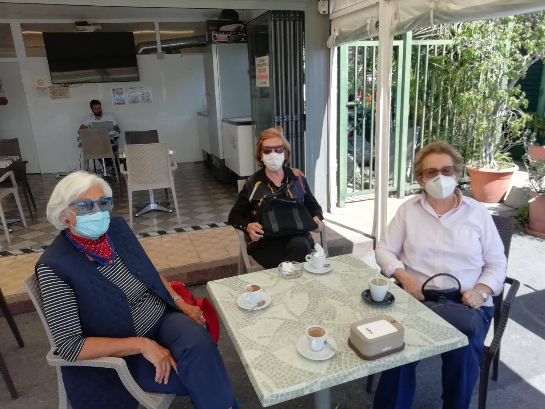 Maria, Vittoria et Marika (de gauche à droite) prennent un café en terrasse.