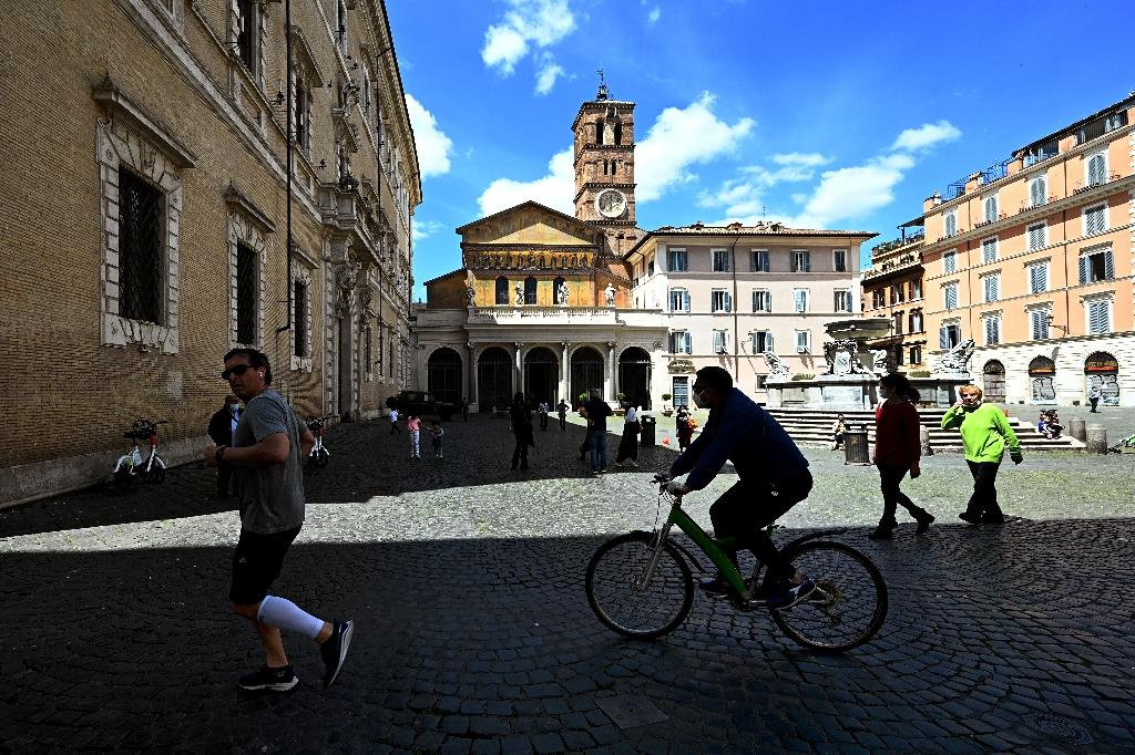 Un homme fait du vélo et un autre court, sur une place de Rome, le 3 mai 2020