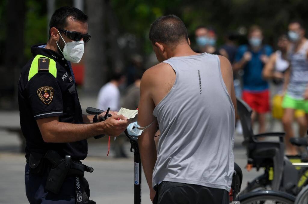 Un policier municipal effectue un contrôle du port du masque à Barcelone (Espagne) le 9 juillet 2020