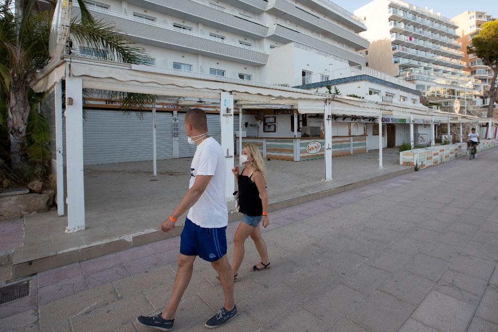 Des touristes passent devant des magasins fermés sur l'île de Majorque, aux Baléares, le 27 juillet 2020.
