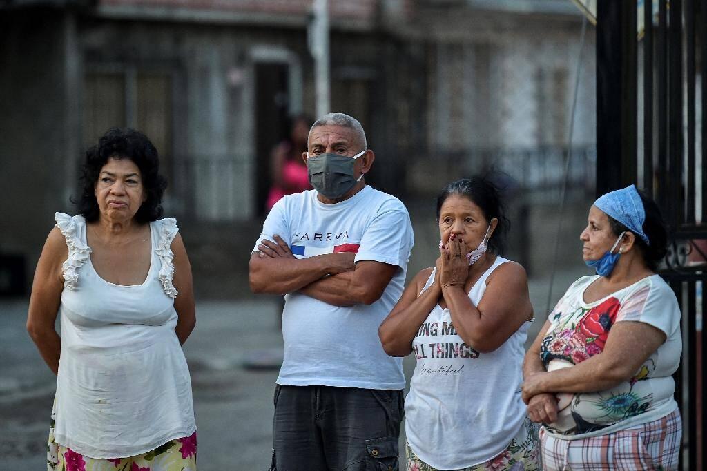 Des riverains observent des employés de pompes funèbres emporter le corps d'un homme probablement décédé du Covid-19, à Cali (Colombie), le 26 juillet 2020