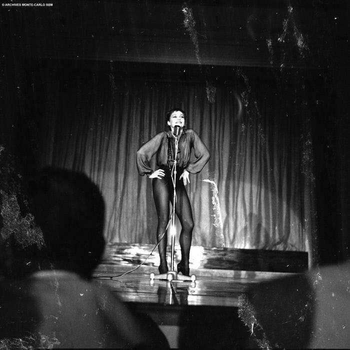 En 1957, la danseuse et chanteuse expose ses longues jambes derrière le micro pour animer une soirée de fête sur la scène du Sporting d'été en Principauté, dont elle est une fidèle à l'époque.
