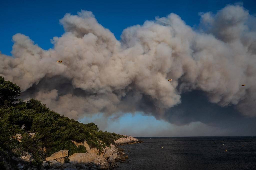Trois Canadair de la Sécurité civile survolent des panaches de fumée, le 4 août 2020 à La Couronne, près de Marseille où un violent incendie ravage plusieurs centaines d'hectares de végétation