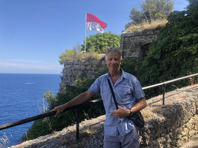 Jean-Marc Ferrie, guide touristique monégasque, devant le Fort Antoine et le drapeau monégasque.