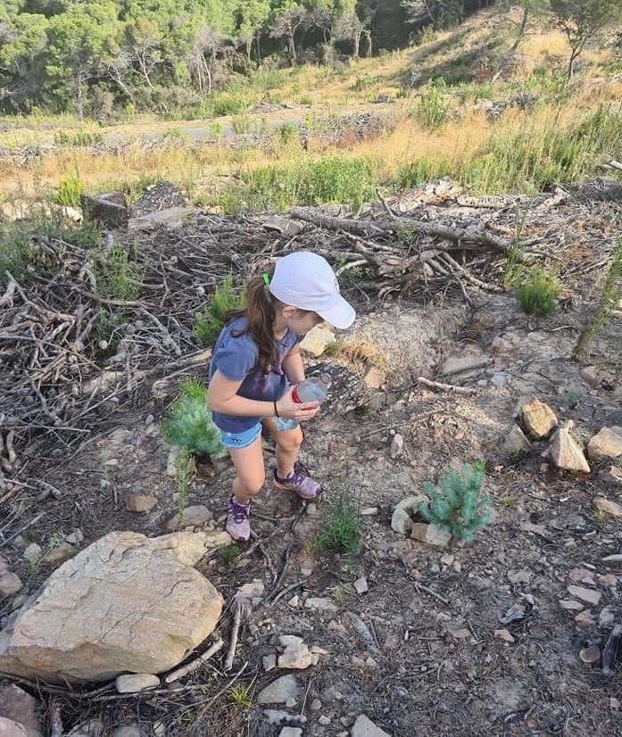 Manon, 8 ans, venue au chevet des jeunes plants forestiers avec sa sœur Julie et ses parents.