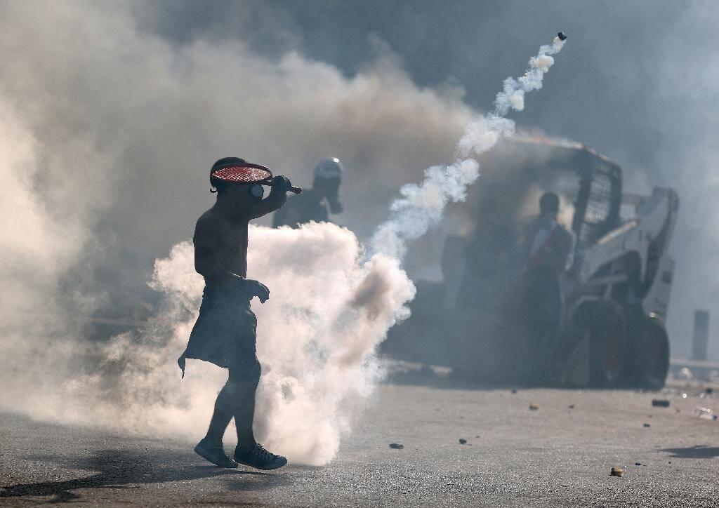 Un manifestant utilise une raquette pour renvoyer une grenade lacrymogène lors de heurts avec la police, le 8 août 2020 à Beyrouth