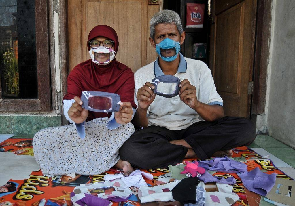 Dwi Rahayu (g) et son mari Elfiandi, tous deux sourds et muets, présentent leurs masques transparents à Yogyakarta, en Indonésie, le 22 avril 2020