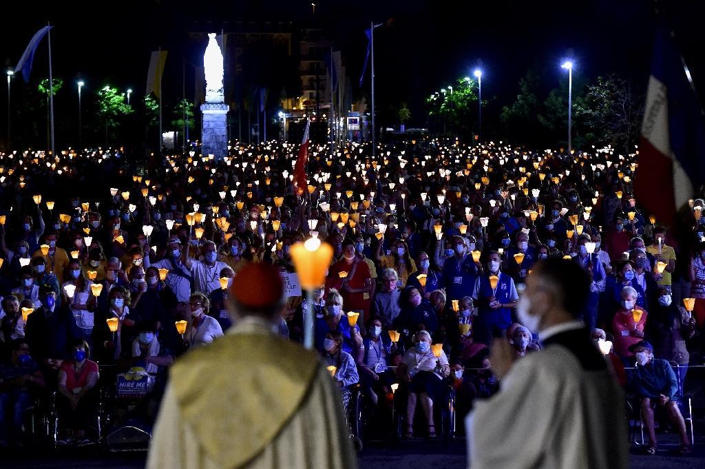 Des pèlerins, masqués, assistent à une messe à Lourdes, le 14 août 2020