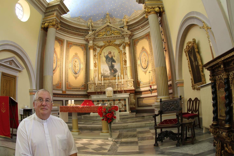 Le révérend Anthony Ingham devant le chœur de la chapelle.