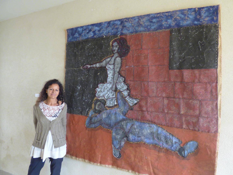 """La Vençoise Corinne Tounsi, une des artistes du """"Camin'Art"""", sous le porche du nouveau centre culturel de Vence, devant une de ses œuvres. Une création élaborée à partir de toiles teintes enrichies de fils teintés et cousus et de fragments de toiles découpées."""
