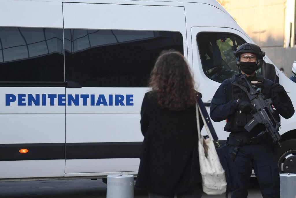 Un policier monte la garde a l'arrivée d'un fourgon qui transporte les accusés du procès des attentats de janvier 2015, au tribunal à Paris le 2 septembre 2020