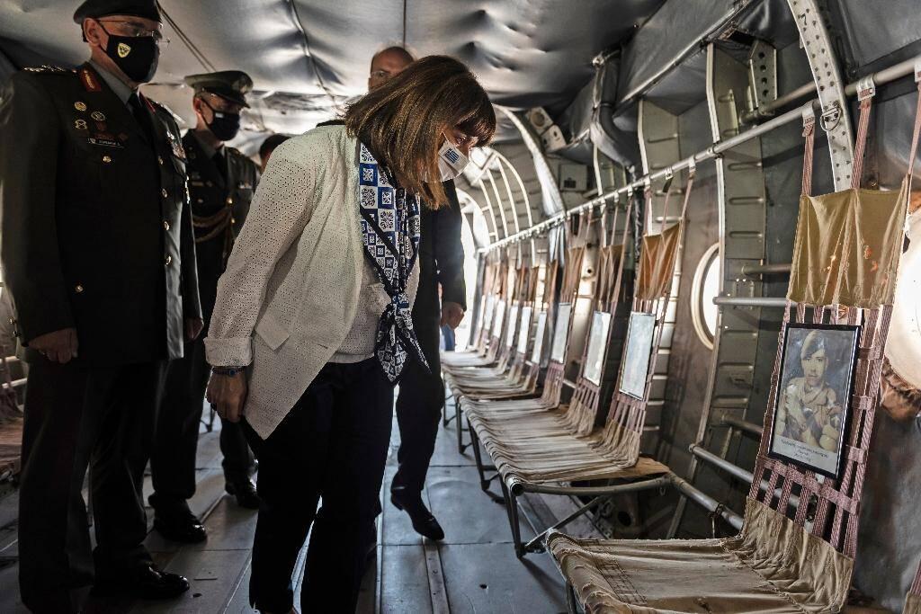 La présidente grecque Katerina Sakellaropoulou  regarde les portraits de soldats dont l'appareil a été abattu par erreur en 1974 pendant l'occupation de Chypre par les forces turques, le 22 septembre 2020 au cimetière militaire de Makedonitissa à Nicosie