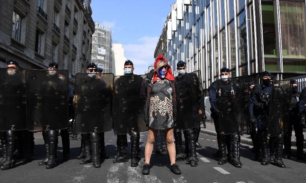 Un manifestant portant un masque de protection devant un cordon des forces de l'ordre , le 12 septembre 2020 à Paris
