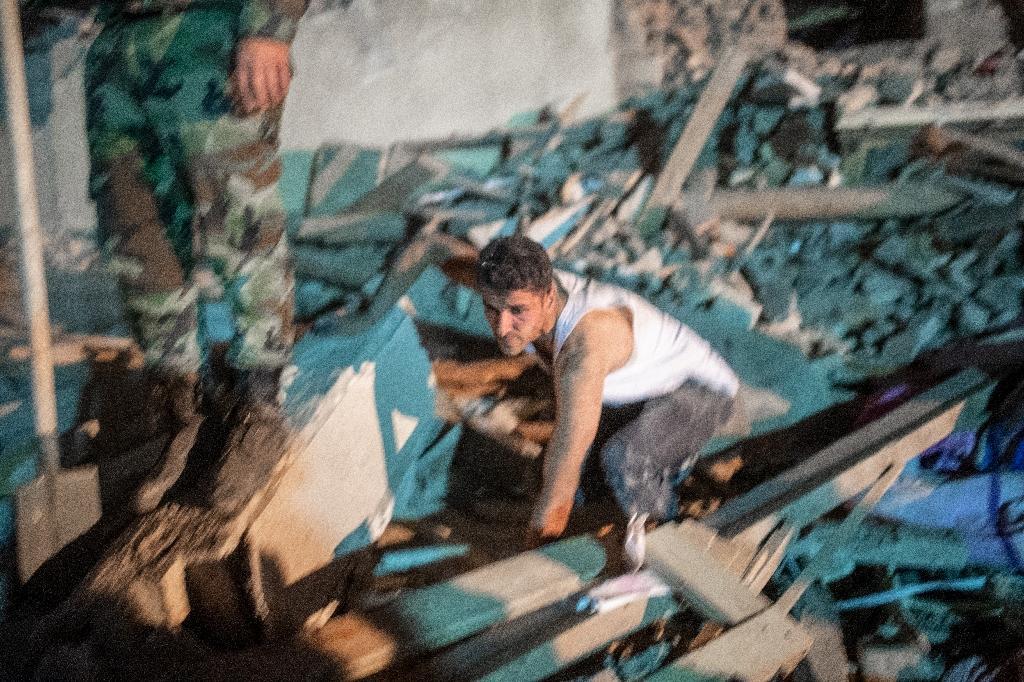 Un homme cherche parmi les débris d'une maison frappée par un missile à Gandja (Azerbaïdjan) le 17 octobre 2020