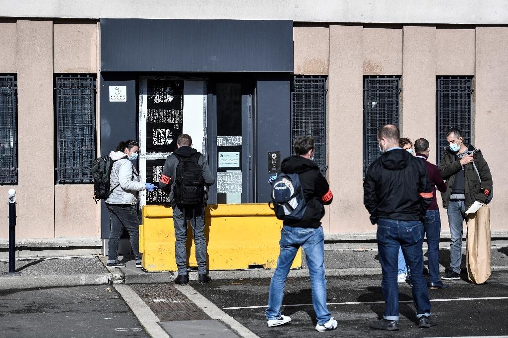 Des policiers devant l'entrée endommagée du commissariat de police de Champigny-sur-Marne, le 11 octobre 2020