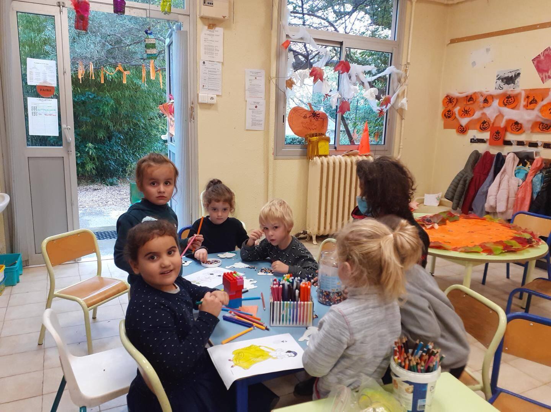 A l'atelier de l'accueil de loisirs, le petitDorian à côté de son animatrice référente participe comme ses camarades à l'atelier de perles.