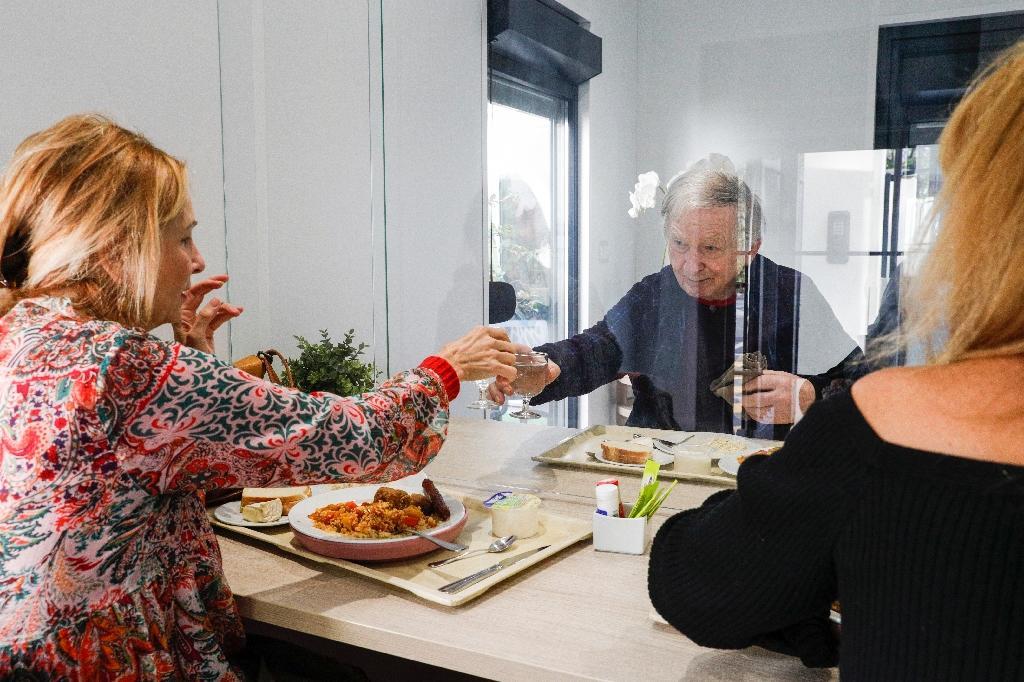 Guy, 93 ans, avec ses deux filles Elisabeth (d) et Véronique dans un mobile-home où ils peuvent déjeuner ensemble, le 12 novembre 2020 à l'Ehpad Beauregard, à Villeneuve-Saint-Georges, près de Paris