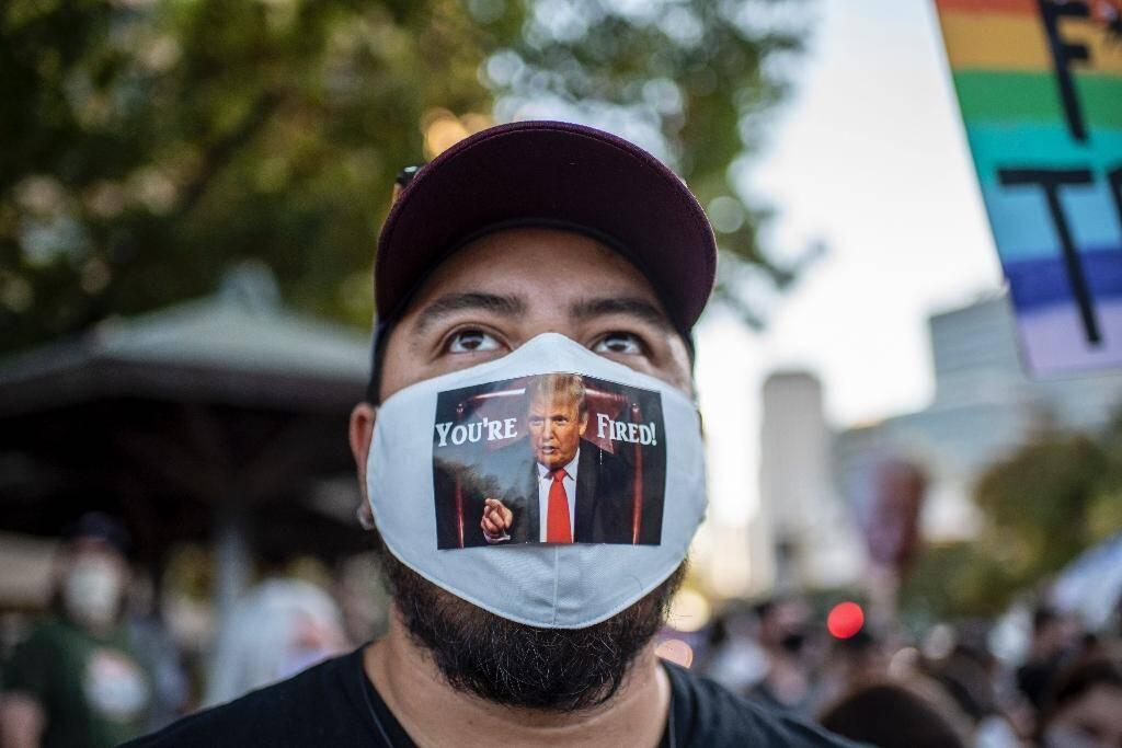 """Un homme porte un  masque sur lequel est écrit """"You're Fired Trump"""" (""""Vous êtes viré Trump""""), le 7 novembre 2020 à Austin au Texas"""