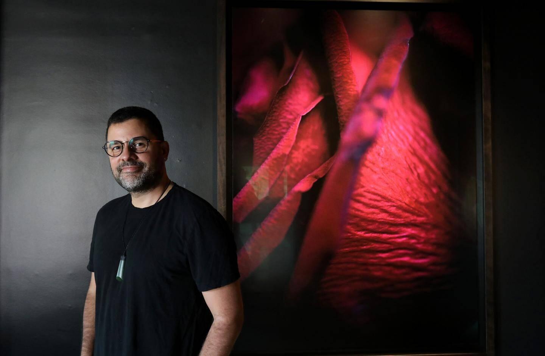 Le photographe devant une photo d'une rose en macro, qui compte parmi ses préférées.