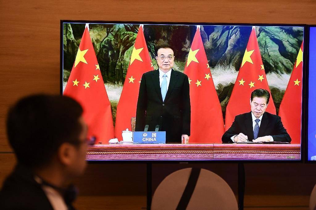 Sur l'image en visio-conférence, le Premier ministre chinois Li Keqiang (au centre) et son ministre du Commerce Zhong Shan (à droite) qui signe l'accord de libre-échange, le 15 novembre 2020
