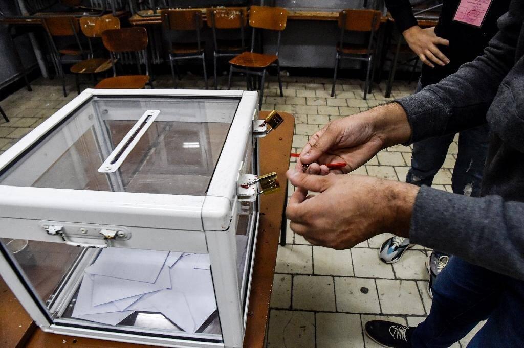 Des assesseurs ouvrent une urne utilisée lors du référendum sur la réforme de la Consitution algérienne à Alger, le 1er novembre 2020