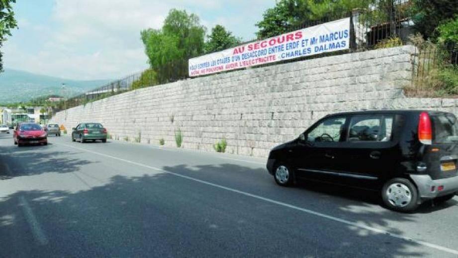 En accrochant une banderole sur la route de Cannes, après Sport 2000, Charles Dalmas espère faire accélérer le raccordement de ses appartements au réseau électrique.(Photo Grégory Ettori)