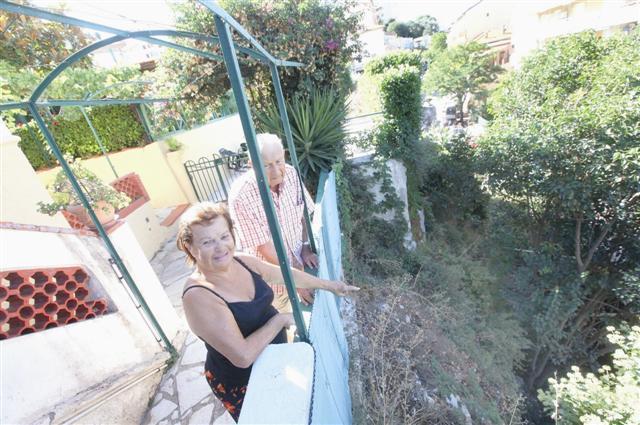Suzanne Barelli et son compagnon, Jean Schlemenson, devant la partie du terrain qui s'est effondrée.
