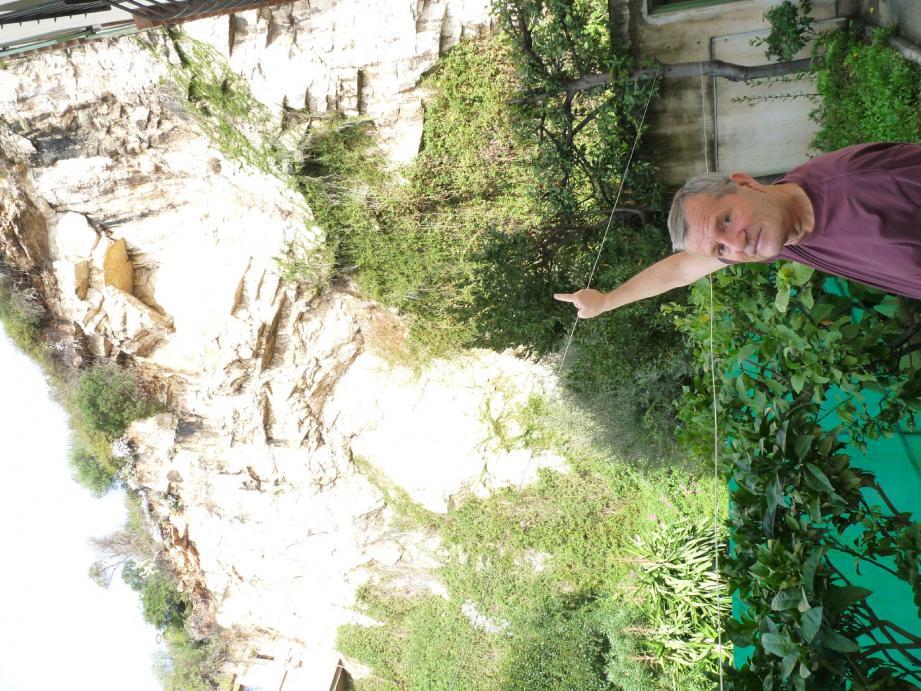 René Maistre habite au pied de la falaise. Il montre du doigt le rocher qui menace tout en haut de la paroi.