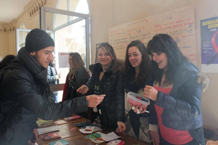 Des lycéennes, membres du club Unesco, tiennent un stand où se vendent préservatif et rubans rouges.
