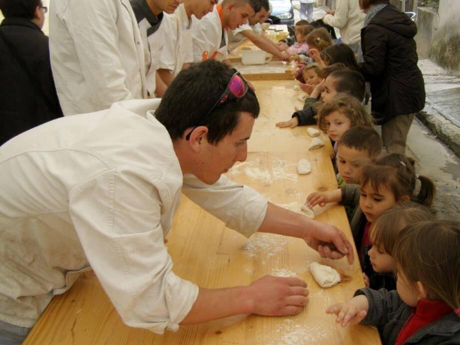 Les élèves du primaire confectionnent leur pain sous la directive de leurs aînés.