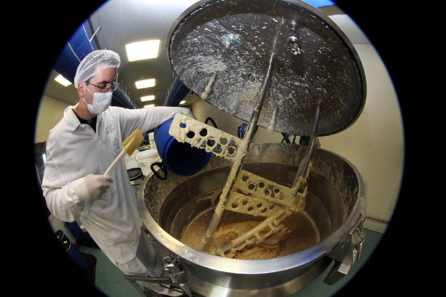 L'opérateur insère les adjuvants dans une cuve de mélangeur.