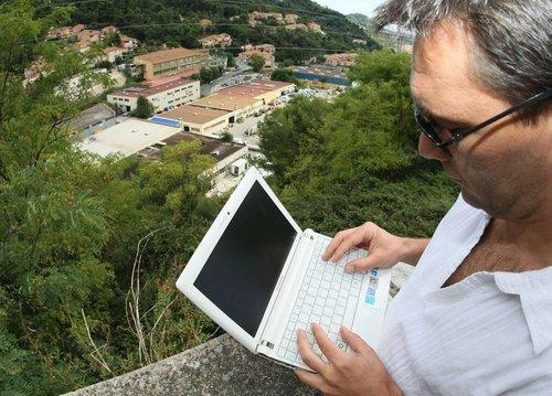 Un homme utilise un ordinateur portable à Menton.
