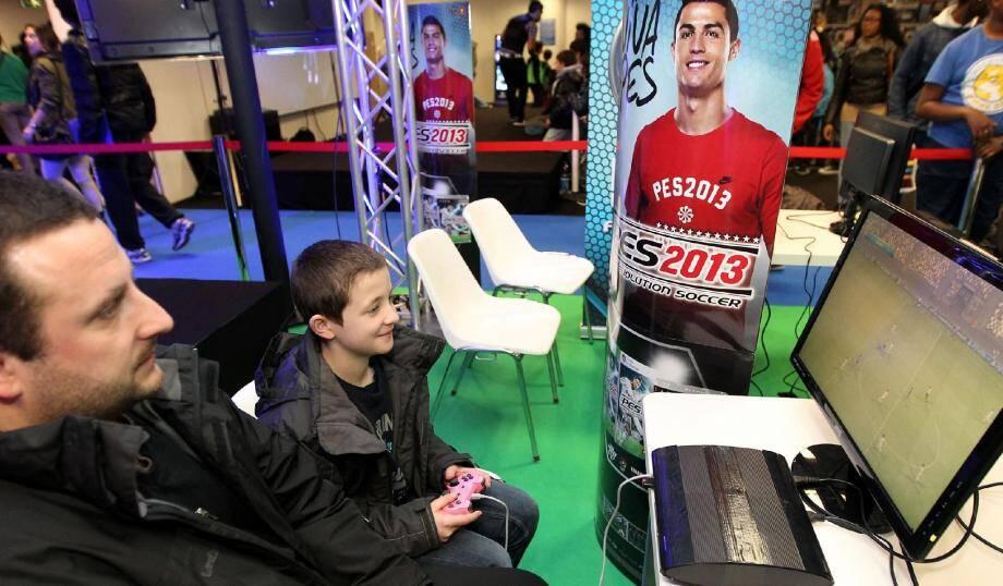 Adulte et enfant, c'est un peu la totalité du public qui se retrouve sur les jeux vidéo qu'ils soient en ligne ou pas. Ici, un jeu de simulation de foot sur le stand de PES.