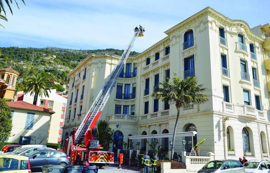 Une opération de reconnaissance sur les toits est menée par les pompiers à l'aide de la grande échelle.